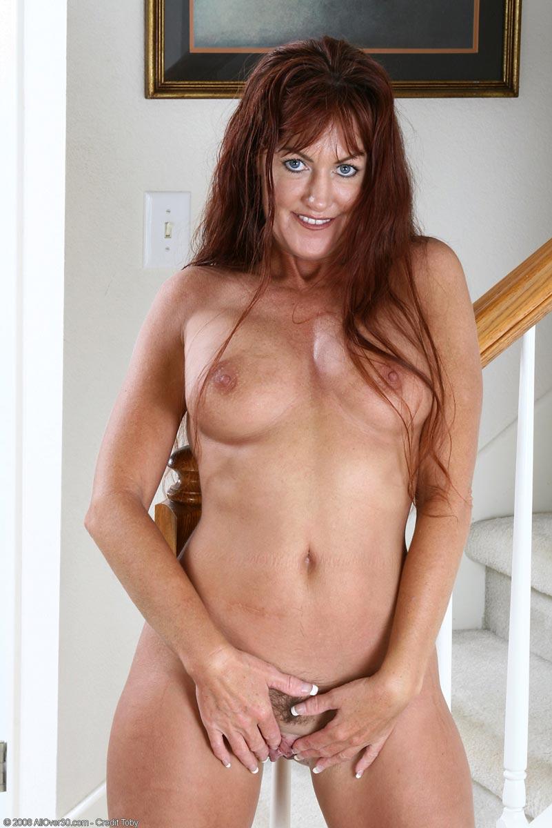 Curvy redhead caught stripping